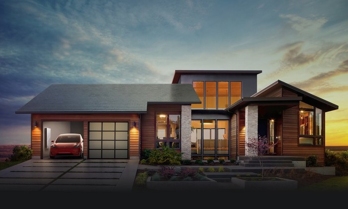 Home with a solar roof and a Tesla in the garage.