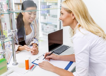 Pharmacist and customer in drugstore