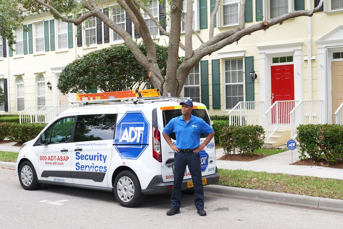An ADT installer stands with his hands on his hips in front of an ADT van parked alongside a row of townhouses.
