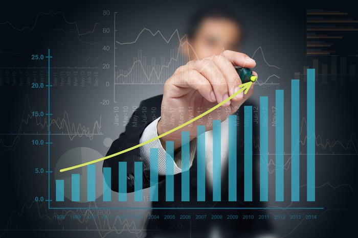 A businessman in a suit draws an upward sloping line above an ascending column chart.
