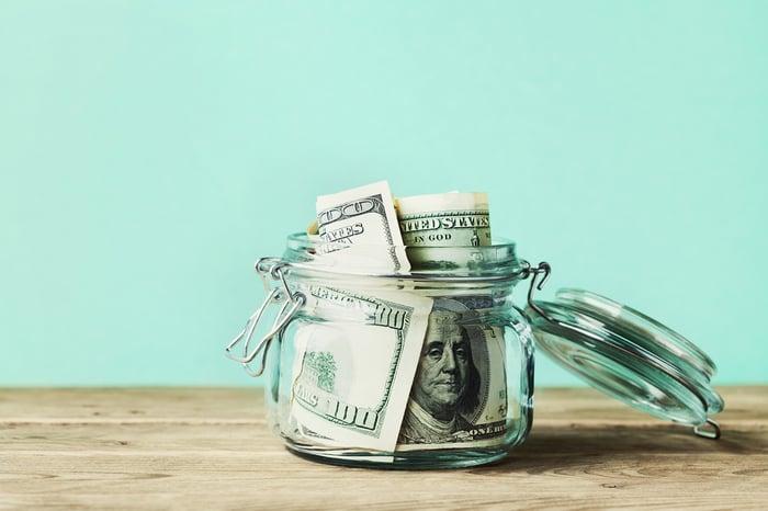 $100 bills in a transparent glass jar.