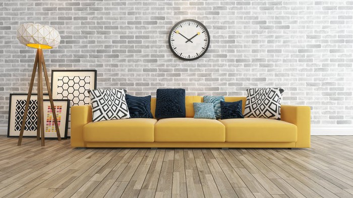 Living room with wood flooring, couch, and a large wall clock on a gray brick wall