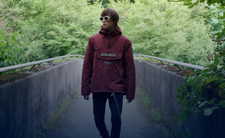 Young man on forest bridge with dark sunglasses wearing a Napapijri brand jacket.