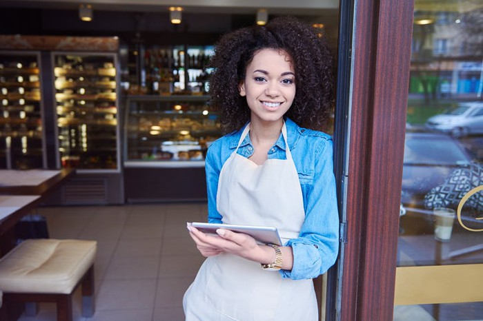 Young female coffee shop owner in apron at storefront, holding tablet.