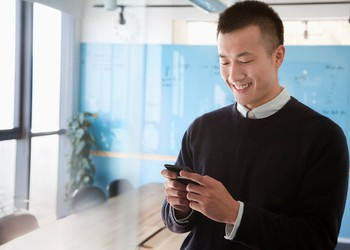 Young Chinese Man Smiling While Chatting on Mobile Phone