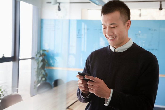 Young Asian man smiling while chatting on mobile device.