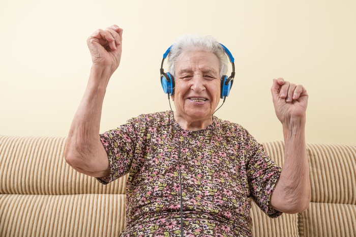 A happy senior woman listening to headphones and raising her arms as if dancing.