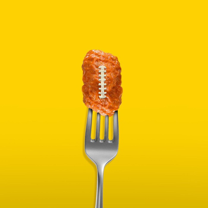 Boneless chicken wing shaped like football on a fork