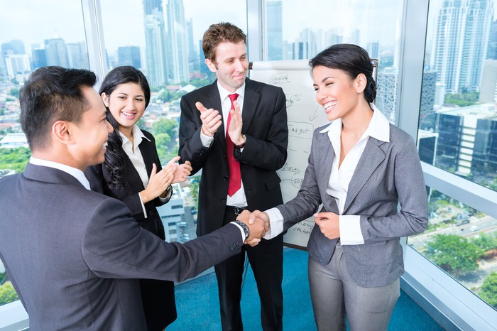 Professional male and woman shaking hands while two other professionals look on and clap