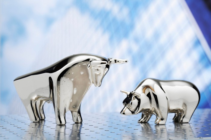 Small chrome bull and bear statues facing one another.