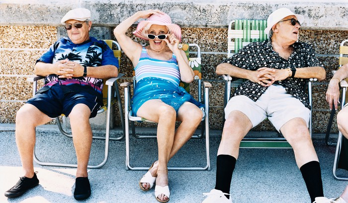 Three senior citizens in summer clothes sitting and chatting on folding lawn chairs.