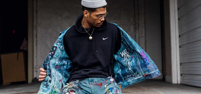 An artist poses in a Nike sweatshirt.