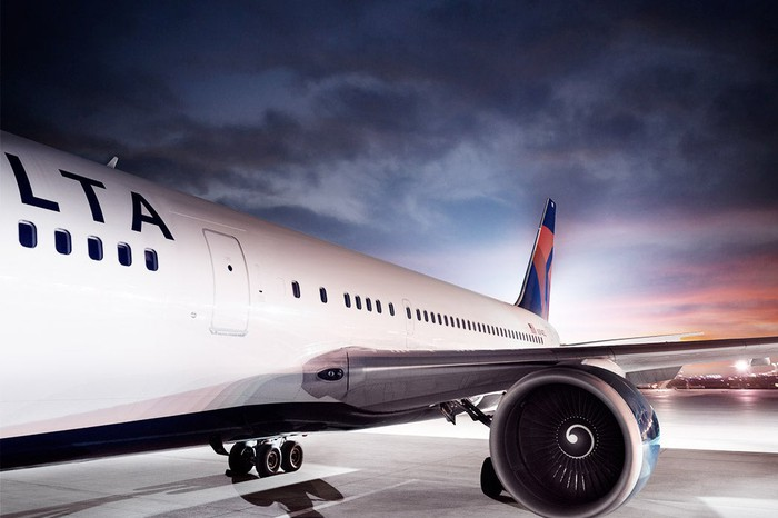 Left side of a Delta airliner on a hangar floor under a cloudy sky near dusk.