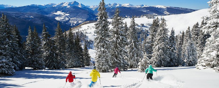 Skiers heading down a mountain at Vail.