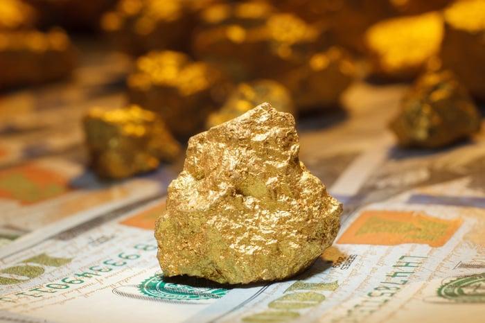 A big gold nugget sitting on $100 bills.