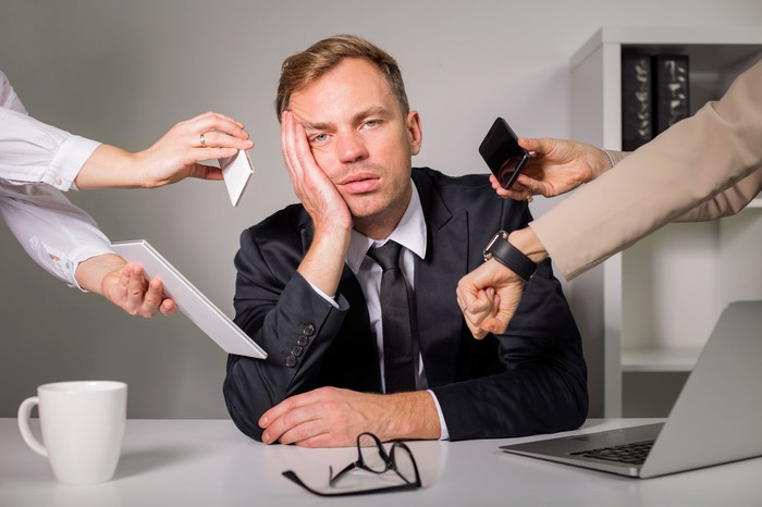 Professional with tired expression at desk with multiple people sticking various objects in his face