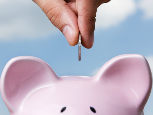 putting a coin into a piggy bank_GettyImages-125183558