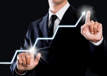 Businessman pointing to lighted chart