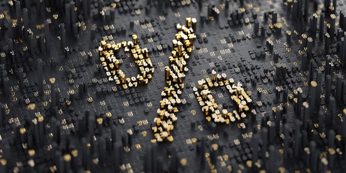 Percentage sign in raised gold mosaic against a gray background.