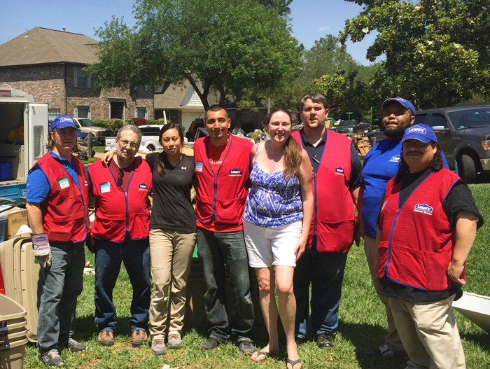 Lowe's employees gathered on a lawn in a residential neighborhood helping a family.