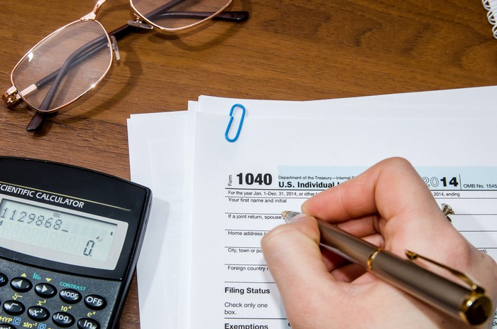 A person holding a pen while filling out tax forms