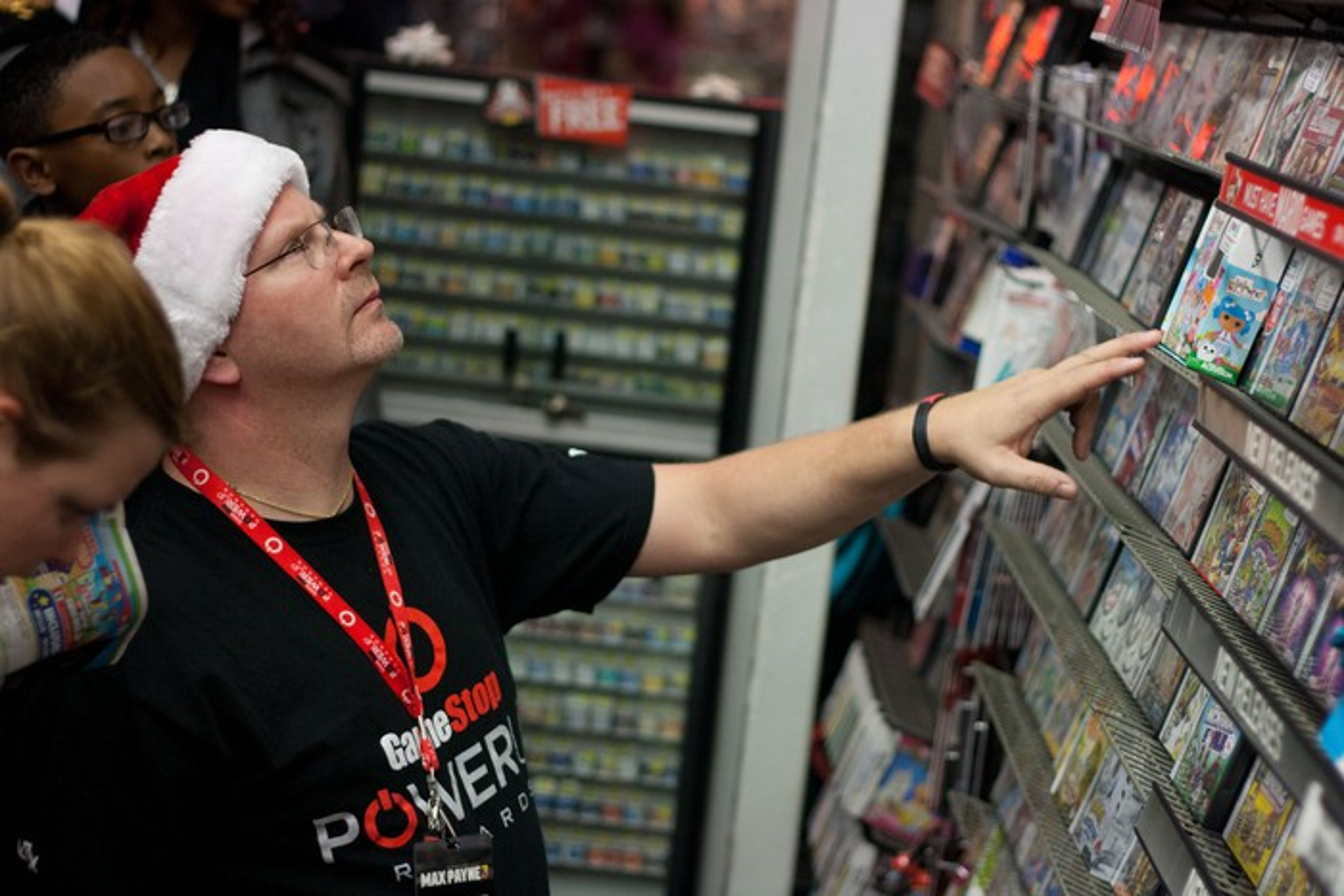 GameStop employee wearing a Santa hat and helping customers
