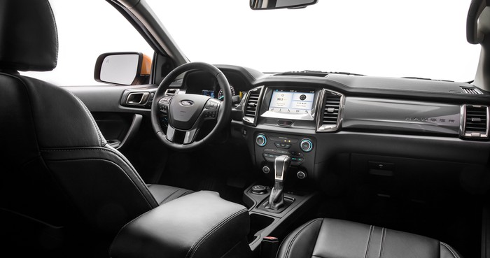 A view of the front seat and dash of the 2019 Ford Ranger Lariat. The seats have leather upholstery and the dash features a prominent touchscreen.