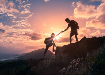 Male and female hikers climbing up mountain cliff and one of them giving helping hand