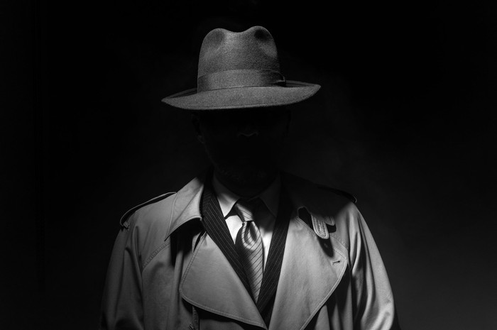 A person whose face is obscured wearing a trenchcoat, suit, tie, and fedora.