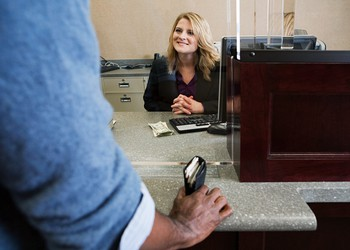 bank teller smiling at customer who has wallet in hand