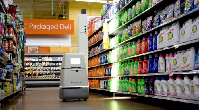 A small robot navigating down a store aisle while scanning items on the shelves.
