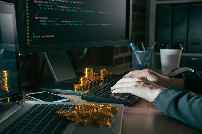 """Mined cryptocurrency tokens """"appearing"""" around a computer."""