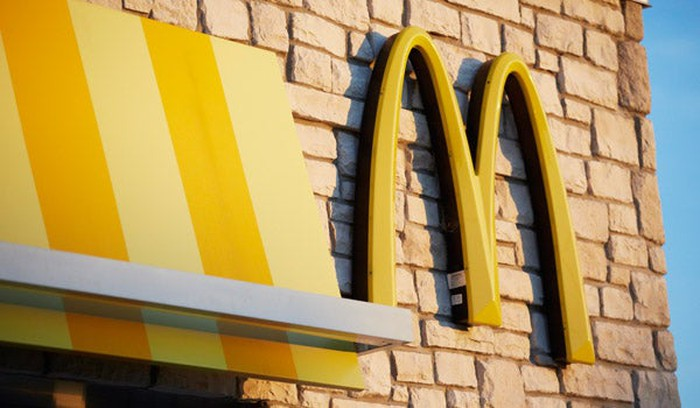The side of a McDonald's restaurant, closeup on the company's golden arch logo.