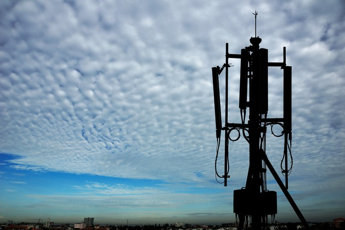 A radio transceiver atop a cell tower against cloudy skies and a faraway city skyline.