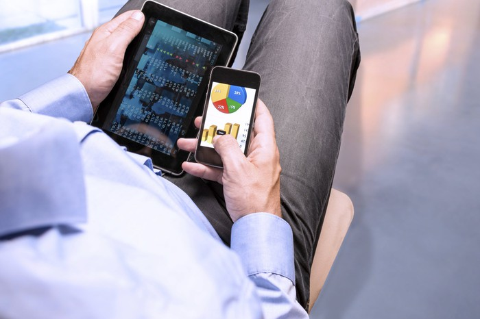 A man using a tablet and a smartphone.