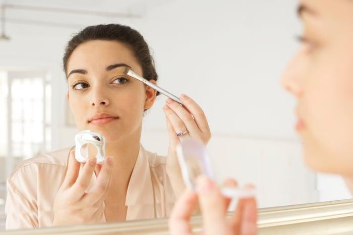 A woman applies makeup in a mirrior.