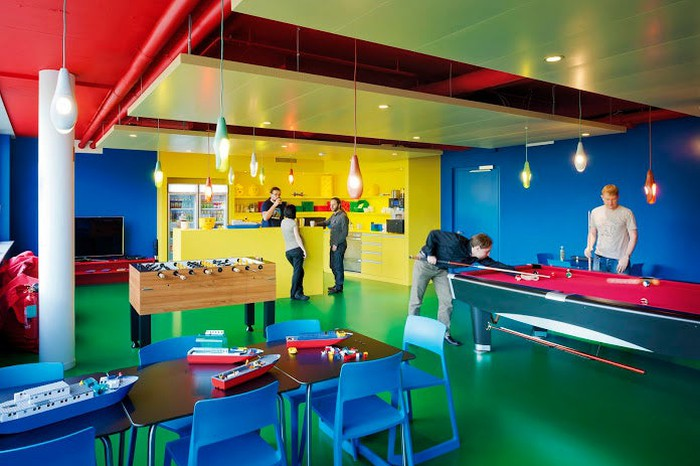 Workers relaxing in a brightly colored break room in Google's primary colors, featuring a pool table and some foosball action.