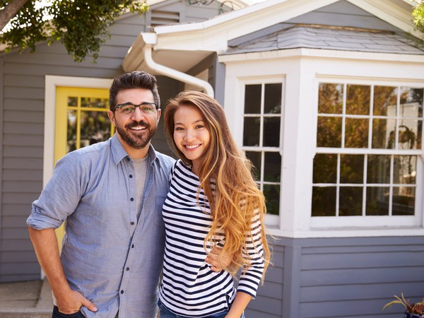 young man and woman standing in front of house with arms around each other and smiling -- couple new home homeownership real estate POC