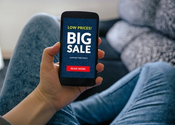 A person holding a cell phone that reads Low Prices Big Sale limited time only read more