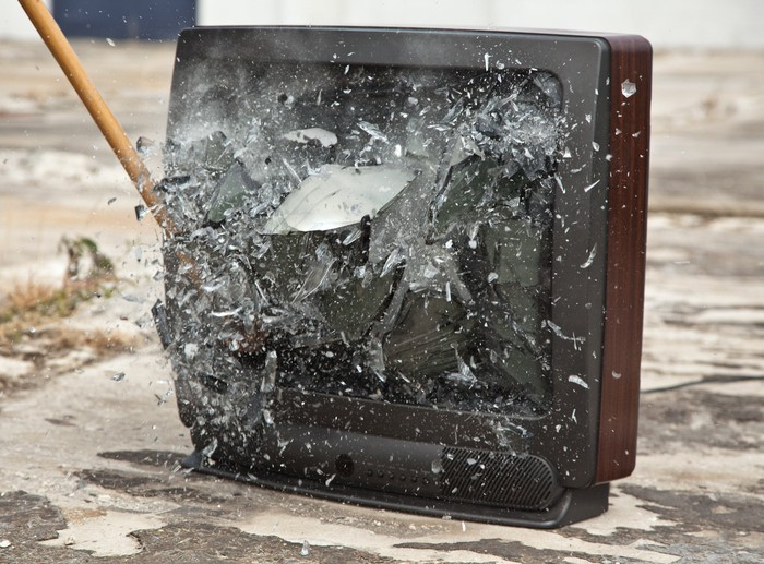 A tool shatters the glass of a TV set.