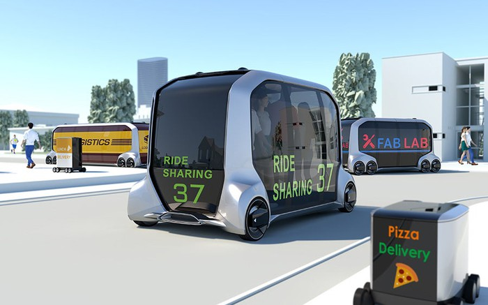 An artist's rendition of a mobile world. Different sizes of e-Palette, a box with wheels and mostly made of tinted glass windows, are on the road. Some of them are carrying mail, one pizza, another a ride-sharing service, and another a mobile retail store.