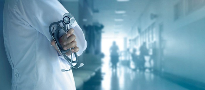 Medical professional in a white coat holding a stethoscope standing along the wall of a medical facility hallway with people out of focus in the distance.