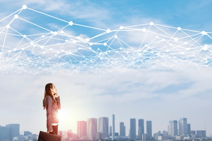Businesswoman gazes at a city skyline with a web of white lines interconnected above.