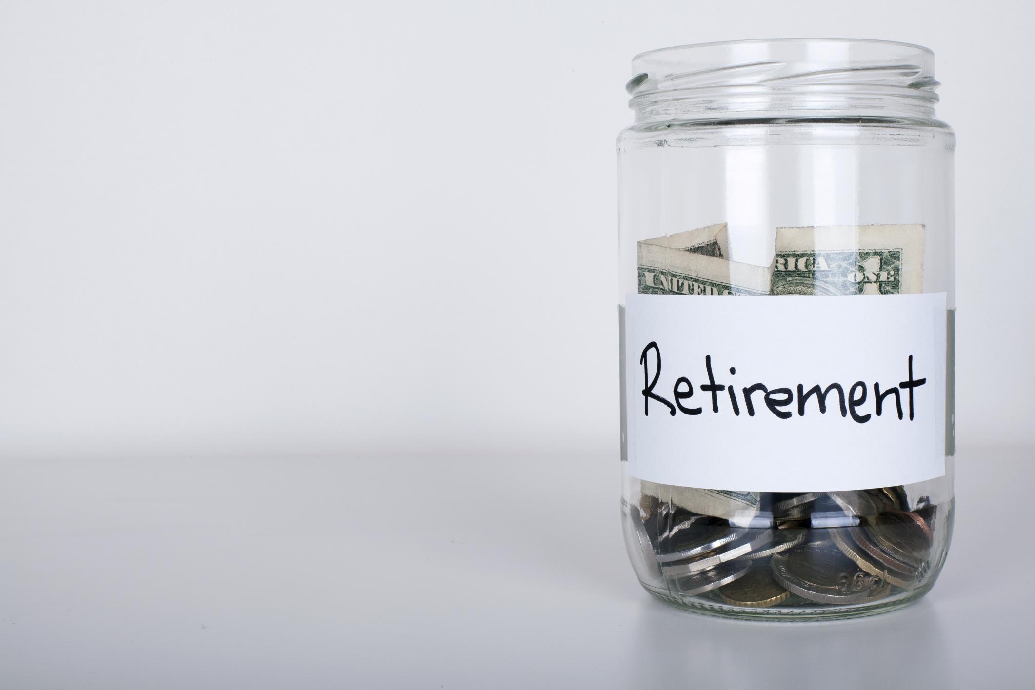 Glass jar of money labeled retirement.