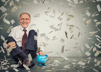 Man on floor with money raining