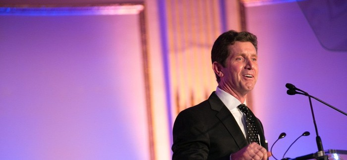 Johnson & Johnson CEO Alex Gorsky standing at a stage in front of a purplish backdrop.