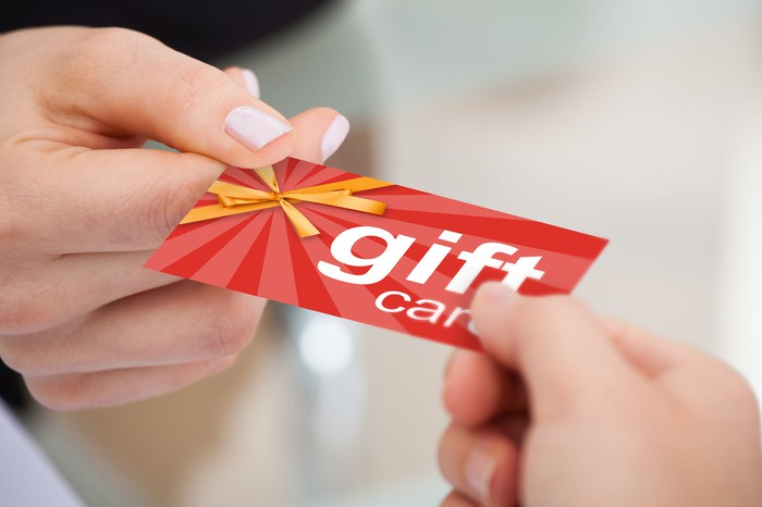 One person handing a gift card to another.