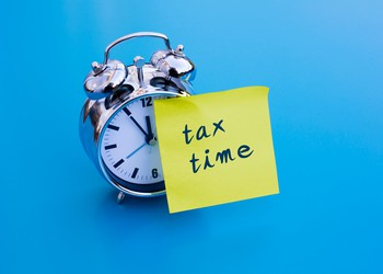 alarm clock with tax time post it_GettyImages-492538188