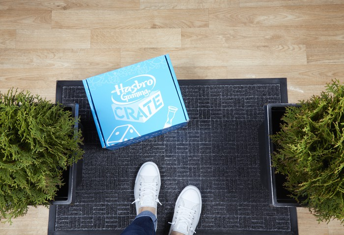 A blue box sitting on a door mat labeled Hasbro Gamin Crate.