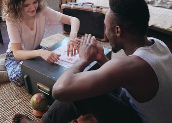 Young couple sitting on carpet playing board game